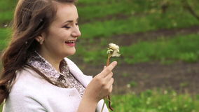 Close up profile of young girl blowing dandelion in the garden. Slowly.  stock video footage