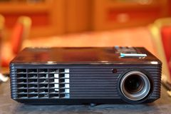 Close up projector in conference room . LCD Projector technology video presentation and home Entertainment object . mini led proje. Mini led projector on wood royalty free stock photography