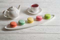 Close up. Provence breakfast. Colorful pastry macarons laid out on an oblong plate, a cup of berry tea, a teapot stock photography
