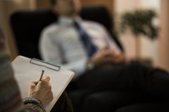 Close-up of psychotherapist writing diagnosis. Close-up of psychotherapist writing a diagnosis while analyzing patient stock image