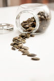 Close up of pumpkin seeds spilling out of glass jar Royalty Free Stock Photo
