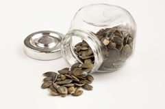 Close up of pumpkin seeds spilling out of glass jar Royalty Free Stock Photos