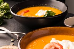 Close up pumpkin soup with shrimps, pumpkin seeds in dark bowls and bread, silver spoons stock image