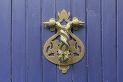 Close-up Punho do vintage para bater em uma porta de madeira azul sob a forma de duas serpentes contorcendo fotos de stock