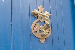 Close-up Punho do vintage para bater em uma porta de madeira azul sob a forma de duas serpentes contorcendo foto de stock