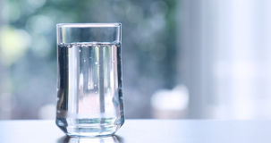 Close up  purified fresh drink water from the bottle on table in Stock Image
