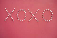 Close-up of push pins in formation of x and o over pink background depicting hugs and kisses Royalty Free Stock Photography