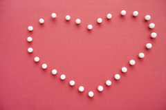 Close-up of push pins forming heart shaped over pink foreground Stock Photos