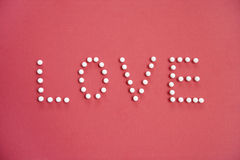 Close-up of push pins spelling love over colored background Royalty Free Stock Photos