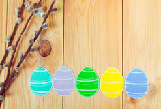 Close-up of pussy-willow branches and colorful paper eggs silhouette frames against wooden background.  Stock Photography