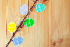 Close-up of pussy-willow branches and colorful paper eggs silhouette frames against wooden background.  Stock Photos