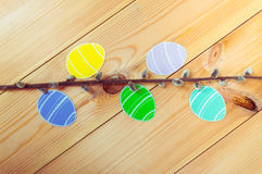 Close-up of pussy-willow branches and colorful paper eggs silhouette frames against wooden background.  Royalty Free Stock Photo