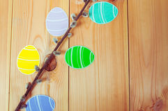 Close-up of pussy-willow branches and colorful paper eggs silhouette frames against wooden background.  Royalty Free Stock Image