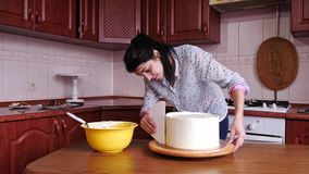 Close-up of woman putting cream on a chocolate sponge cake by hand using spatula. Close-up of putting cream on a chocolate sponge cake by hand using spatula stock footage