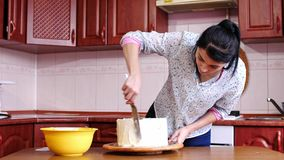 Close-up of woman putting cream on a chocolate sponge cake by hand using spatula. Close-up of putting cream on a chocolate sponge cake by hand using spatula stock video