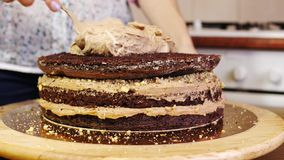 Close-up of putting cream on a chocolate sponge cake by hand using spoon. Home baking. Cake on a rotating stand to decorate cakes stock footage