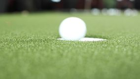 Close-up putting small golf ball into hole playing professional sport golfing. Close-up putting small golf ball into hole high angle. Golfer enjoying playing stock video