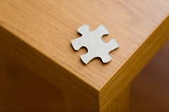 Close up of puzzle piece on wooden surface Royalty Free Stock Photography