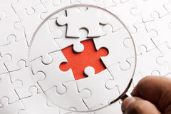 CLOSE UP Puzzle pieces with a magnifying glass. Concept image of detecting a defect. Royalty Free Stock Image