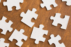 Close up of puzzle pieces on wooden surface Stock Images