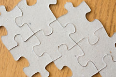 Close up of puzzle pieces on wooden surface Royalty Free Stock Images