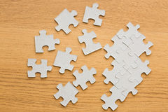 Close up of puzzle pieces on wooden surface Stock Photos