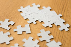 Close up of puzzle pieces on wooden surface Royalty Free Stock Photography