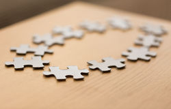 Close up of puzzle pieces on wooden surface Royalty Free Stock Image