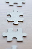 Close up of puzzle pieces on wooden surface Royalty Free Stock Photo