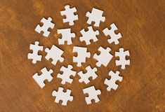 Close up of puzzle pieces on wooden surface. Business and connection concept - close up of puzzle pieces on wooden surface Royalty Free Stock Photo