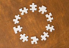 Close up of puzzle pieces on wooden surface. Business and connection concept - close up of puzzle pieces on wooden surface Royalty Free Stock Photos
