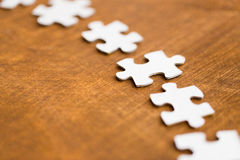 Close up of puzzle pieces on wooden surface Stock Photography