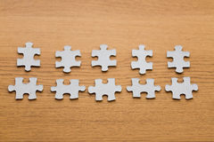 Close up of puzzle pieces on wooden surface Royalty Free Stock Photos