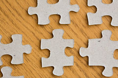 Close up of puzzle pieces on wooden surface Stock Image