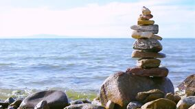 Pyramid of stacked stones on boulder on the inshore waves of Lake Baikal, balance and harmony concept