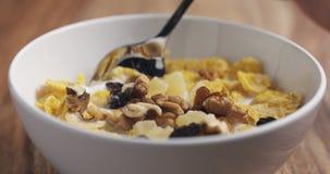 Close up que come com um café da manhã da colher com flocos de milho e mistura de porcas e de frutos Foto de Stock