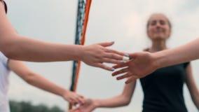 Close-up que cumprimenta as mãos dos jogadores de voleibol das meninas que agradecem ao oponente para o último fósforo no movimen filme