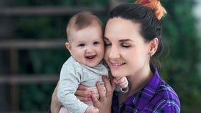 Close-up que importa-se a mãe bonita que tem o sentimento do amor da ternura que beija seus bebê e sorriso pequenos video estoque