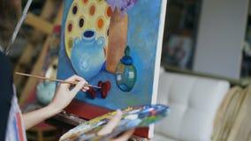 Close-up que segue o tiro da mulher do artista com a escova que pinta ainda a imagem da vida na lona na arte-classe video estoque