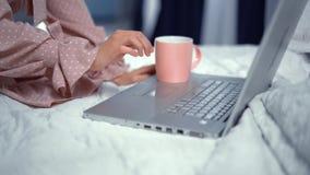 Close-up que veste o vestido cor-de-rosa que senta-se na cama e que trabalha no portátil video estoque