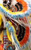 Close Up of Quill and Feather Headdress and Bustle Worn by Fancy Pow Wow Dancer. Close up of an orange, blue, yellow and white feather and quill headdress and royalty free stock photo