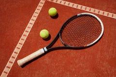 Close up racket and balls on tennis terrain. Close up of racket and balls on tennis terrain at red dross Royalty Free Stock Photos