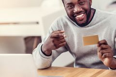 Close up of radian guy posing with golden card. Check this out. Scaled up shot of a millennial African American man grinning broadly while sitting at a table and Stock Photography