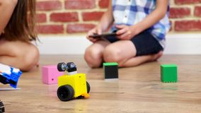 Close-up, radio-controlled robot moves on floor, little geniuses, children play electronic robots, cars, modern toys on. Radio control. new technologies in