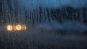 Close Up Rain Drops on Misted Car Window Glass with Blurred Night City Car Lights Bokeh as Background. 4K. Close Up Rain Drops on Misted Car Window Glass with stock footage