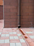Close up on rain gutter downspout pipe for roof runoff with open water drainage in the pavement. Stock Photo