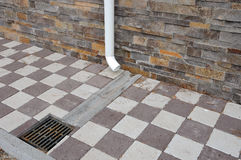 Close up rain gutter. Paving slabs decorative wall and rain gutter. Royalty Free Stock Images
