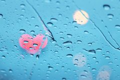 Close up raindrops on surface glasses car with lights traffic heart shape bokeh stock images