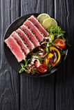 Close up of rare seared Ahi tuna slices with fresh vegetable sal. Ad on a plate. Top view from above vertical Royalty Free Stock Photo