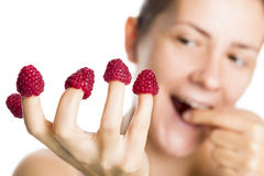 Close up of raspberries on fingers. Royalty Free Stock Photo